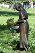 Larger than life-size sculpture of a girl watering flowers.