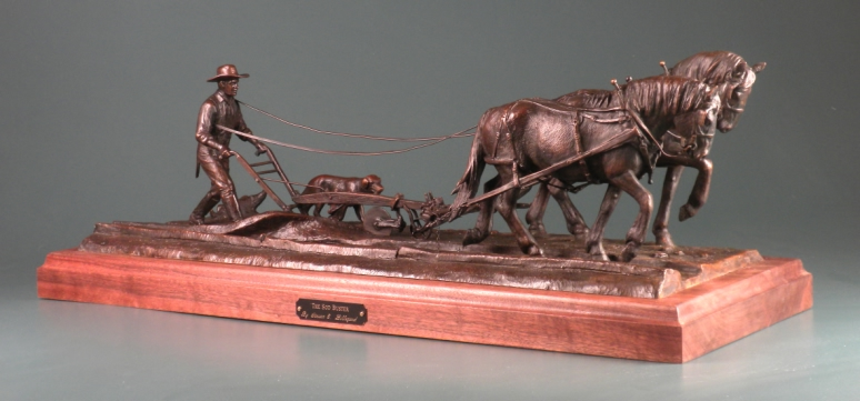 sculpture of man plowing with horses.